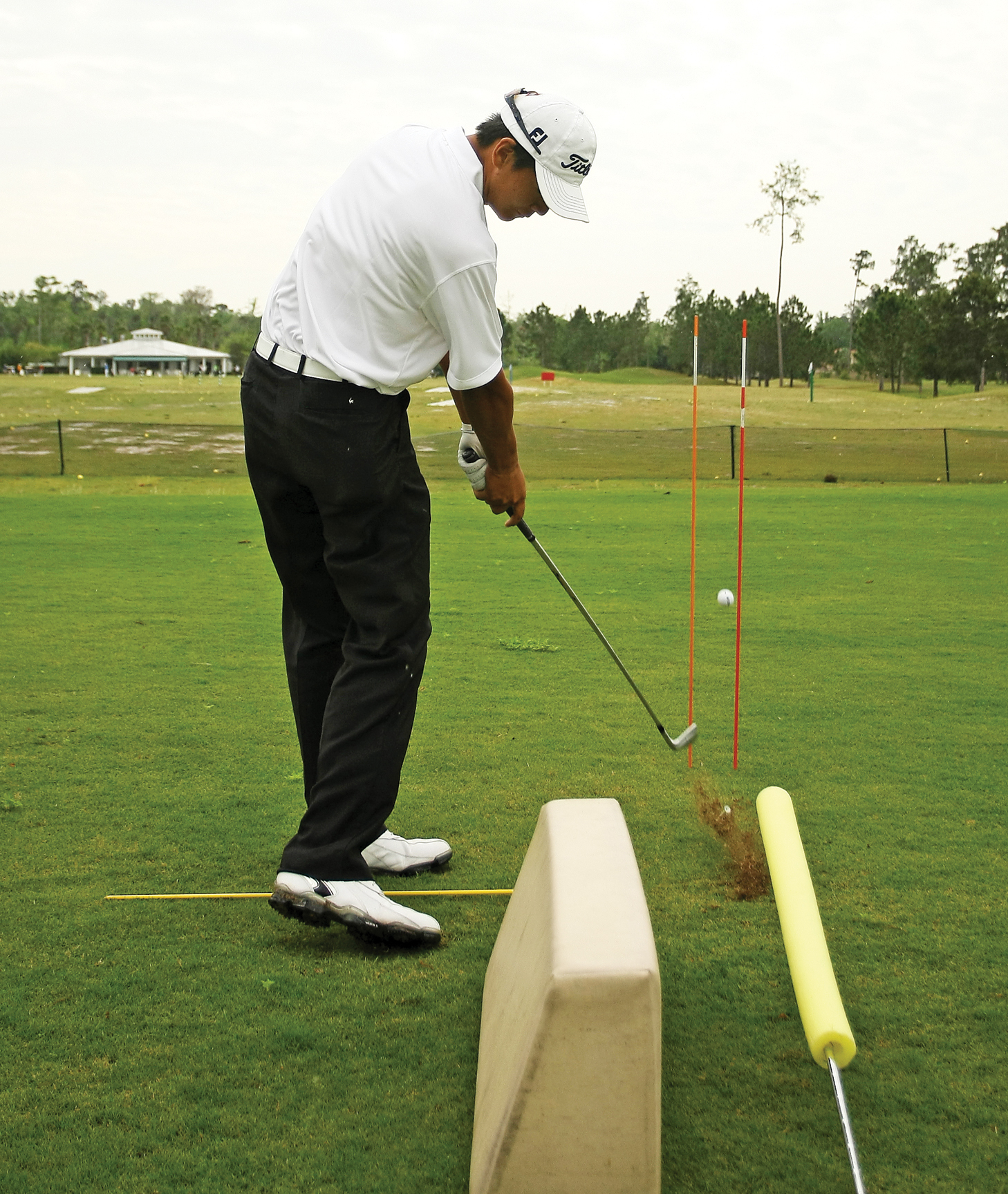 Hak uses a cushion, a padded rod and alignment sticks to work on his aim and swing plane.