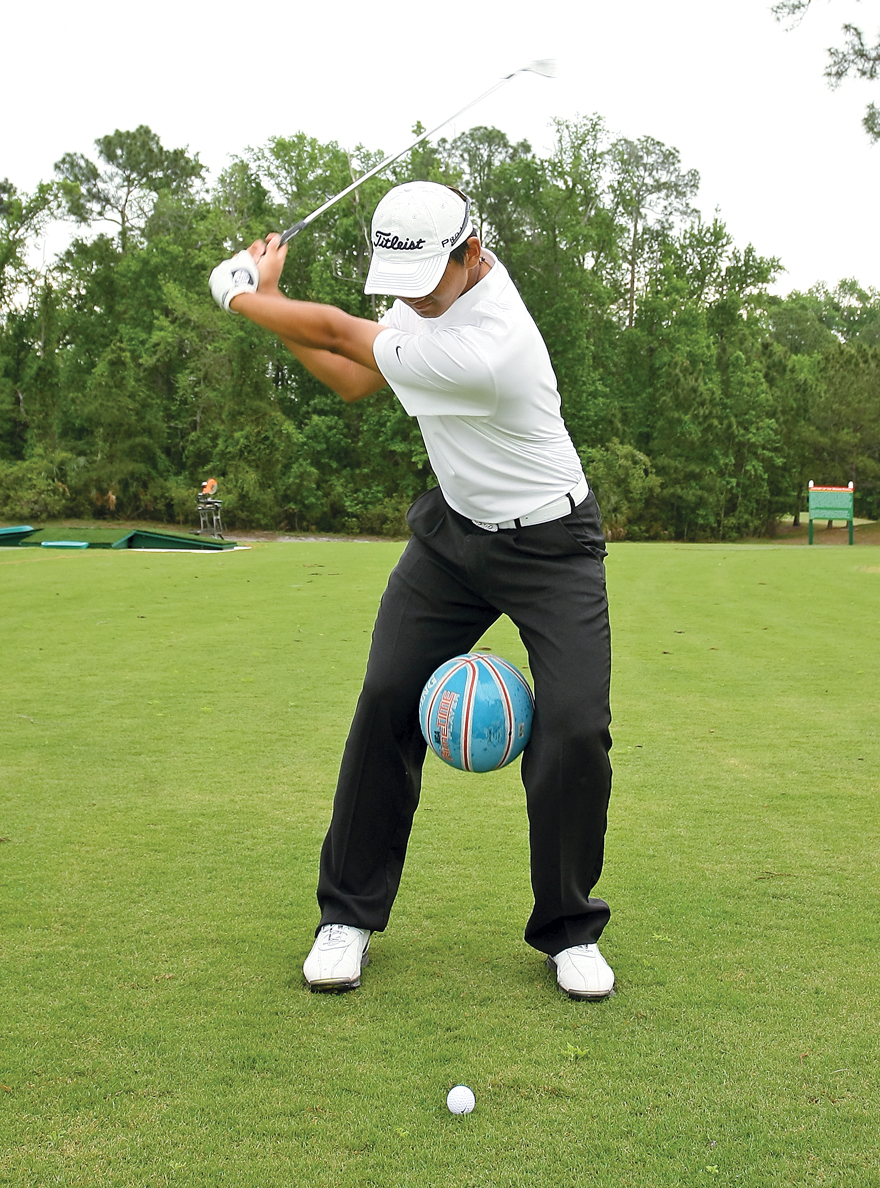 Hak places a soccer ball between his legs, dropping it at the beginning of the downswing.