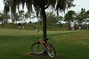 Many students ride bikes across the vast IMG campus. This one waits just off the practice putting green.