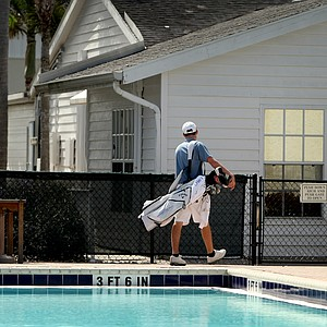 A golfer walks by a pool common area at IMG Academies.