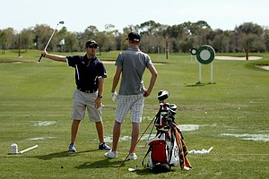 Golf instucor Chad Keohane works with Max Lindholm, 15, on the range at the IMG Golf Academy.