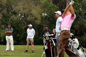 IMG golf coaches watch some of their students as they participate in a practice competition at IMG Golf and Country Club.