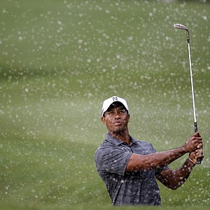 Tiger Woods watches his shot from a 10th hole bunker during the first round of the Players Championship golf tournament, Thursday, May 10, 2012, at Sawgrass in Ponte Vedra, Fla.
