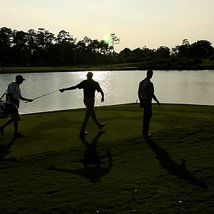 Matt Kuchar and Harris English are silhouetted as they walk down 18 fairway on Saturday at The Players Championship at TPC Sawgrass.