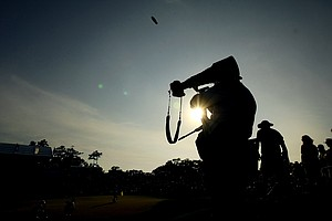 Photographers are silhoutted at No. 18 as the last group finishes on Saturday at The Players Championship at TPC Sawgrass.