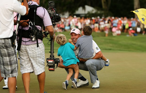 Matt Kuchar embraces his sons, Cameron and Carson as they run onto the green after he won The Players Championship at TPC Sawgrass.
