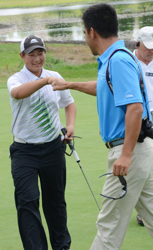 Carl Yuan, 15, gets a congratulatory fist bump after a two-putt par on the ninth hole gave Yuan the last qualifying spot at a U.S. Open local qualifier at Timacuan Country Club in Lake Mary, Fla.