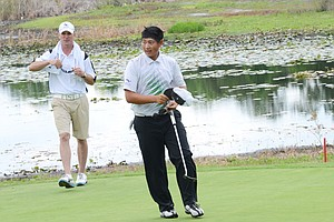 Carl Yuan, 15, walks off the green after a two-putt par on the ninth hole gave Yuan the last qualifying spot at a U.S. Open local qualifier at Timacuan Country Club in Lake Mary, Fla.