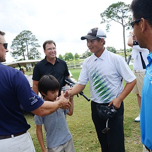 Carl Yuan, 15, is greeted by coaches, Tim Sheredy, left, and Bill Nelson, middle, after a two-putt par gave Yuan the last qualifying spot at a U.S. Open local qualifier at Timacuan Country Club in Lake Mary, Fla.