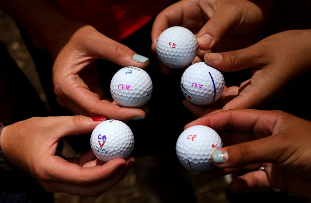 Virginia golfers put the initials of their assistant coaches daughter, Cassidy Bailey, 12,  on their golf balls on Tuesday. She suffers from Dystonia a movement disorder.