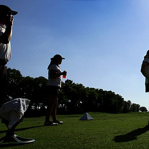 Alabama's head coach, Mic Potter, Hannah Collier, Stephanie Meadow and assistant coach Susan Rosenstiel watch from the driving range as a hot air balloon makes a pass on Wednesday. Alabama is currently leading the championship.