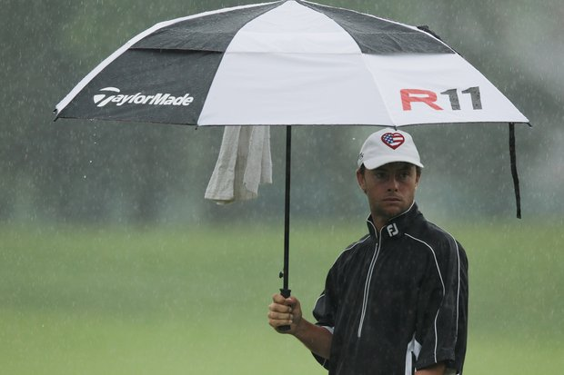 Spencer Levin waits under an umbrella on the seventh hole during the second round of the Memorial Tournament.
