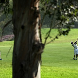 Oregon's Eugene Wong, far right, hits his second shot at No. 18 as head coach Casey Martin and assistant Brad Lanning watch during the first day of Match Play at the 2012 NCAA Championship.