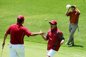 Alabama head coach Jay Seawell runs to hug Bobby Wyatt after he chipped in at No. 18 to win his match during the finals of match play at the 2012 NCAA Championship.
