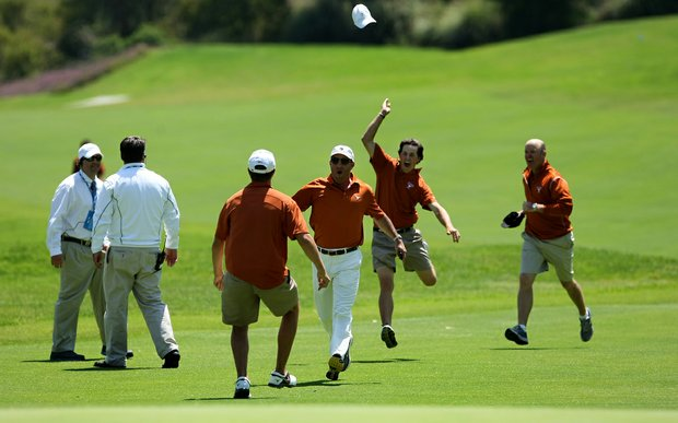 Cody Gribble of Texas tosses his hat as he runs down the fairway after Dylan Frittelli sunk a birdie putt at No. 18.
