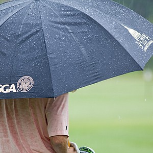 A golfer stands beneath and umbrella during the 2012 U.S. Open Sectional Qualifying at The River Club in Suwanee, Ga.