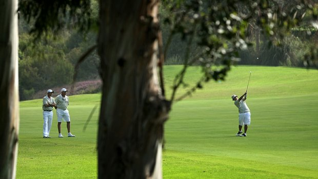 Oregon's Eugene Wong, far right, hits his second shot at No. 18 as head coach Casey Martin and assistant Brad Lanning watch during the first day of Match Play.