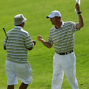 Oregon head coach, Casey Martin, congratulates his player, Eugene Wong during the first day of Match Play at the 2012 NCAA Championship. The Ducks advanced to the semifinals.