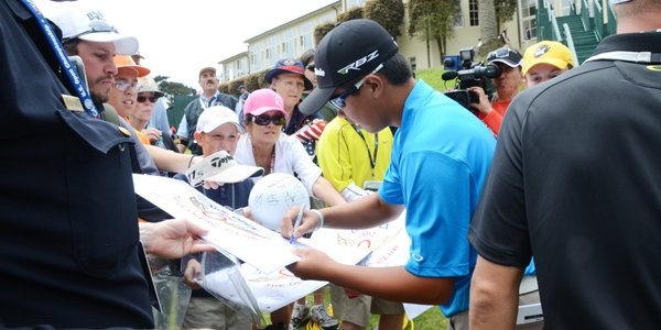 Andy Zhang, 14, signs autographs behind the eighth green at the end of his practice round at The Olympic Club in San Francisco.