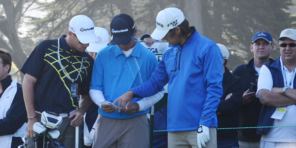 Andy Zhang, middle, goes over yardages with caddie Christopher Gold, left, and Aaron Baddeley at the par-4 18th at Olympic Club in San Francisco.