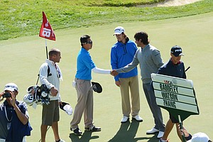 Andy Zhang, left, shakes hands with Bubba Watson, right, after Watson finished up his final hole of the day, the par-4 18th hole at Olympic Club in San Francisco.