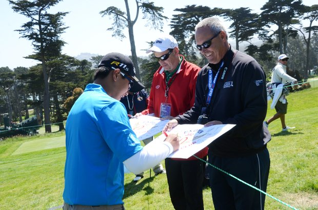 Andy Zhang, 14, signs his first autographs for Jim Carey (red) and Craig Davis (black) at Olympic Club in San Francisco.