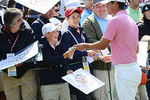 Brooks Koepka signs autographs behind the 8th green at the conclusion of his Wednesday practice round at Olympic Club in San Francisco. The fan received a signed Koepka glove.