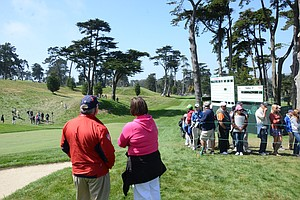 Denise Jakows visits with a marshal as she watches her son, Brooks Koepka, tee off at the par-3 8th hole at Olympic Club in San Francisco.