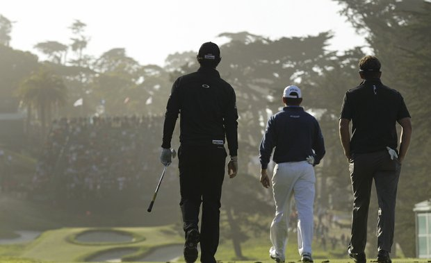 Rory McIlroy (left to right), Lee Westwood and Luke Donald make their way to the 18th hole at The Olympic Club.