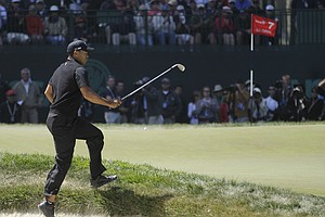 Tiger Woods jumps out of a bunker on the seventh hole during the second round of the U.S. Open Championship golf tournament Friday, June 15, 2012, at The Olympic Club in San Francisco.
