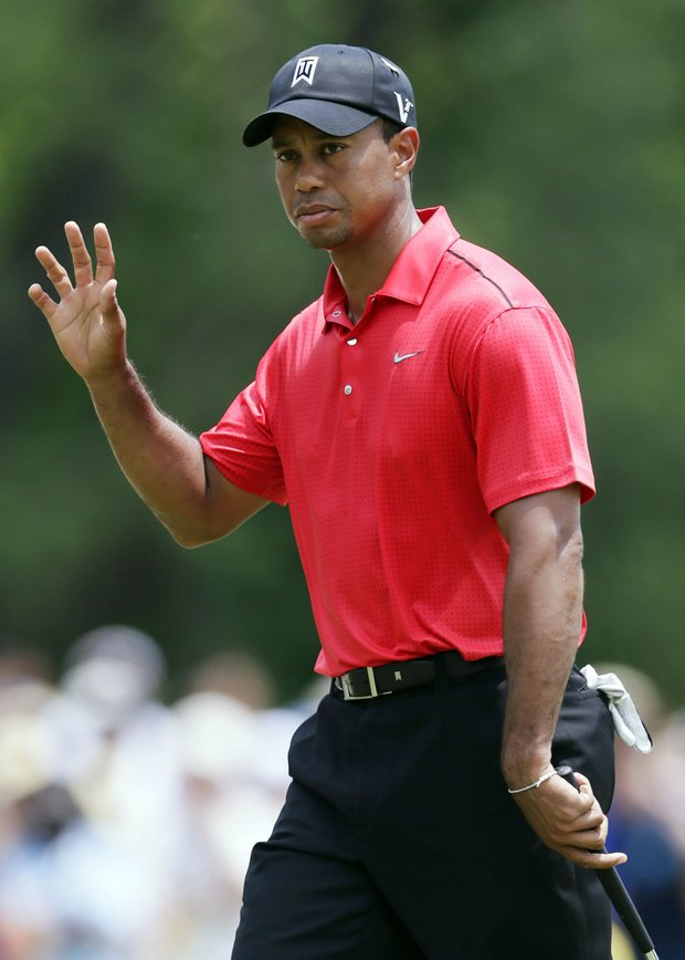 Tiger Woods acknowledges the gallery after making par on the first green during the final round of the AT&T National.