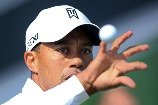 Tiger Woods reaches for a golf ball on the practice ground during the third practice round prior to the start of the 141st Open Championship at Royal Lytham & St. Annes.