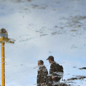 Spectators are reflected in a puddle following heavy overnight rain during the second round of the 141st Open Championship at Royal Lytham & St. Annes Golf Club.