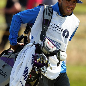 Manchester City's Argentinian footballer Carlos Tevez carries the bag of Andres Romero of Argentina on the 13th fairway during the final round of the 2012 Open Championship at Royal Lytham and St. Annes.