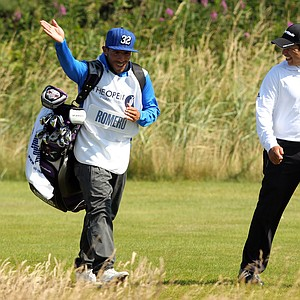 Manchester City's Argentinian footballer Carlos Tevez acting as a caddie for Andres Romero, gestures on the 13th fairway during Romero's final round at the 2012 Open Championship at Royal Lytham and St. Annes.