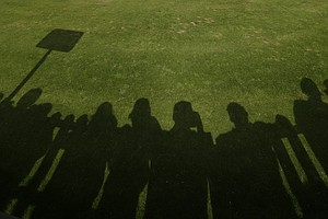 The shadows of spectators are seen on the practice putting green at Royal Lytham & St. Annes Golf Club during the final round at the Open Championship.