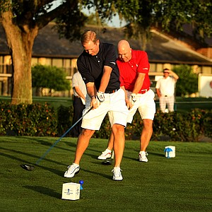 West captain, Jason Miller, left, and East captain, Mark Oskarson right, hit their tee shots at the start of the 2012 Wyndham Cup at Bay Hill Club and Lodge.