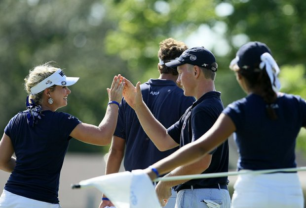 Lindsey Weaver high fives teammate Brade Dalke of the West team on Wednesday during the afternoon mixed four-ball matches.