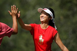 Yu Liu high-fives West team member Tae Wan Lee as she passes hole No. 11 on Wednesday during the morning foursome matches. Liu and partner Karen Chung halved their match. East and West is tied heading into afternoon.