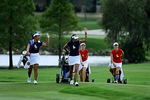 Amy Lee, left, and Alison Lee, right, of the West team wave to fellow team members as they walk to No. 13 on Wednesday during the morning foursome matches. West won the match 2-up. The teams are tied heading into the afternoon.