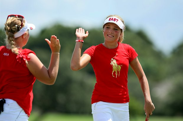 Sierra Brooks of East team high fives her partner, Samantha Wagner after they won hole No. 13 to go 1-up on Wednesday against West's Sierra Sims and Summar Roachell during the morning foursome matches. The teams are tied heading into afternoon matches.