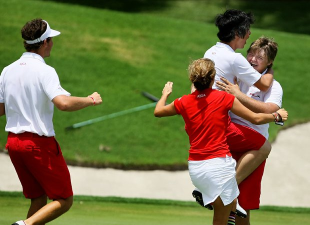 The East's Cody Proveaux is mobbed by his teammates after he won his singles match against Brad Dalke clinching the 2012 Wyndham Cup.