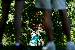 Jayvie Marie Agojo of the Philippines is framed by spectators as she hits her tee shot at No. 10 during the second round of stroke play at the 2012 U. S. Women's Amateur Championship.