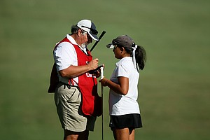 10-year-old, Latanna Stone of Valrico, Fla., talks with her dad/caddie Michael during the second round of stroke play at the 2012 U. S. Women's Amateur Championship. Stone was the youngest to qualify for a Women's Amateur but missed the cut.
