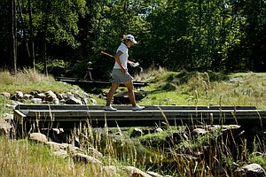 Lydia Ko of Australia crosses a pedestrian bridge at No. 11 during the second round of stroke play at the 2012 U. S. Women's Amateur Championship. Ko placed second in stroke play.