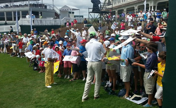 Jonathan Byrd, left, and Matt Kuchar sign autographs behind the 18th green on Tuesday at the Ocean Course.