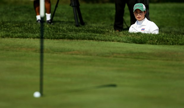 Moriya Jutanugarn watches from the greenside bunker as her ball drops into the hole at No. 16 during the Round of 64 at the 112th U. S. Women's Amateur Championship.