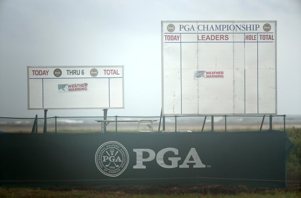 Leaderboards display signs for a weather warning during a practice round of the 94th PGA Championship at the Ocean Course.
