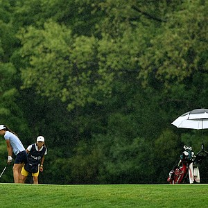 Nicole Zhang's caddie lines her up as the rain starts to come down during the Round of 32 at the 112th U. S. Women's Amateur Championship.