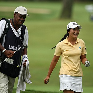 Su-Hyun Oh of Australia with her caddie Flemon Barnes are all smiles after she holed out from the fairway during the Round of 32 at the 112th U. S. Women's Amateur Championship. Oh won her match 5&4.